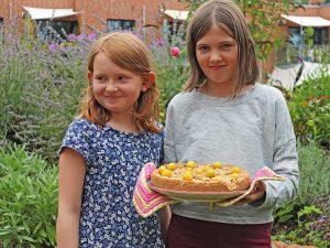 2 Mädchen präsentieren Mirabellenkuchen