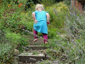 Gartenwall mit kleinem Mädchen