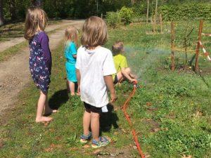 Kinder wässern einen jungen Apfelbaum, ein Regenbogen bildet sich