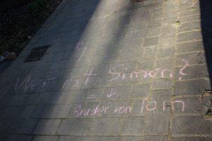 Kreideschrift auf Pflaster fragt: wer ist Simon?