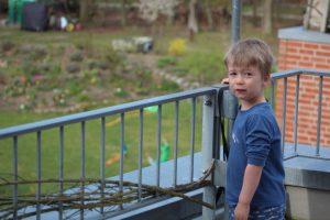 Kind beobachtet Spielszene vom Balkon
