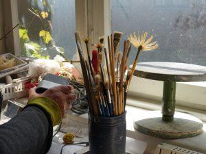 Werkstattblick - Hand greift nach Instrument, Pinsel in Dose